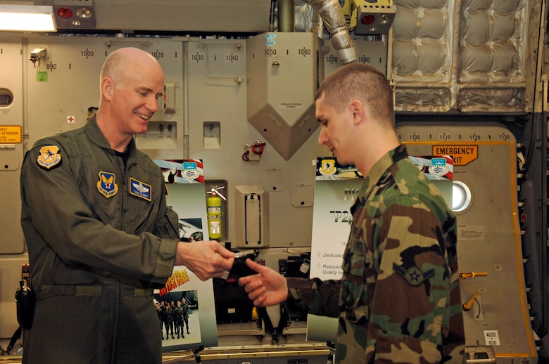 Brig. Gen. S. Taco Gilbert, AFSO 21 chief, gives an AFSO 21 coin to Airman Krystopher Johnson, 437th Maintnenance Squadron crew chief, after Airman Johnson's breifing on the phase plus two lean inititiave at Charleston AFB, S.C., Feb. 16. (U.S. Air Force photo/Staff Sgt. April Quintanilla)