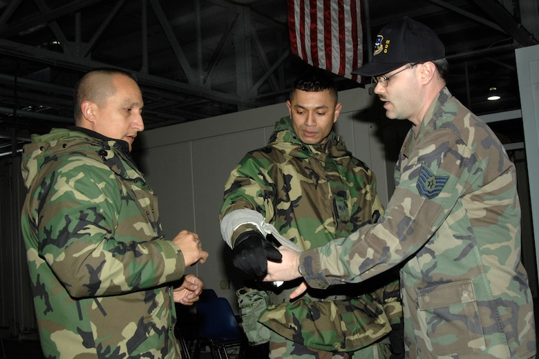 HANSCOM AFB, Mass. -- Tech. Sgt. Robert Cyr, Hanscom Self-Aid and Buddy Care adviser, demonstrates the proper way to wrap an Israeli bandage with the help of 66th Comptroller Squadron personnel Staff Sgt. Robert Mebane and Tech. Sgt. Jose Carrillo. The bandage is among the items included in the Individual First Aid Kit. SABC information begins on page 177 in the Airman's Manual. U.S. Air Force photo by Linda LaBonte Britt