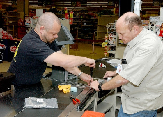 Robert Goupil (left) and David Ketchup from IMB install new registers on Feb. 6 at the commissary on Lackland Air Force Base, Texas. The IMB team replaced the 22 existing registers and installed five additional registers, including using some of the registers to create eight new self-checkout lanes. (USAF photo by Alan Boedeker)