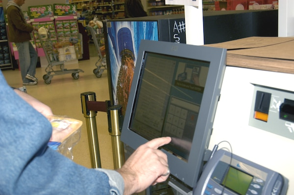 Customers using the new self-check kiosks at the commissary on Lackland Air Force Base, Texas, have the option to scan the barcode, type in the price look-up code or identify the product by image. The Lackland Commissary is one of five testing sites for the new IBM hardware and software systems the Defense Commissary Agency is looking to use worldwide. (USAF photo by April Blumer)