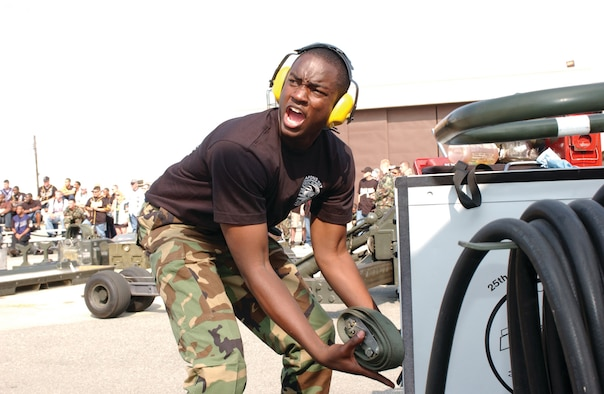 OSAN AIR BASE, Republic of Korea --  Airman Terrance Davis, 51st Aircraft Maintenance Squadron, yells to his teammates as he puts equipment away.  Having finished mounting weapons during the Weapons Load Competition, Airman Davis ensures all the equipment is placed in the correct spot during the timed competition Saturday. (U.S. Air Force photo by  Staff Sgt. Chris Marasky)