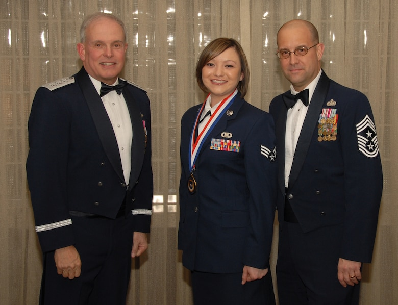 OSAN AIR BASE, Republic of Korea --  Senior Airman Myranda Hinguanzo, 8th Operational Support Squadron, is the 7th Air Force annual winner in the Airman of the Year category. Here she poses with Lt. Gen. Stephen Wood, 7th AF commander, and Chief Master Sgt. Raymond Allen III, 7th AF command chief.
