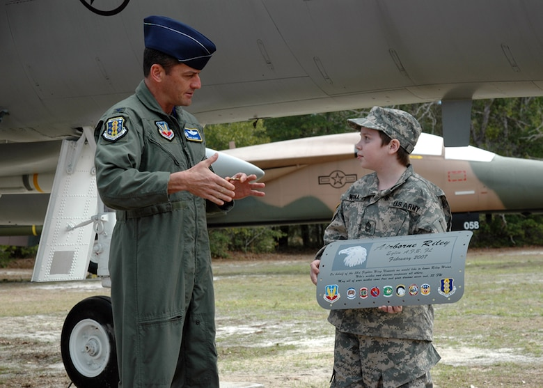 EGLIN AIR FORCE BASE, Fla. -- Col. Russ Handy, 33d Fighter Wing Commander, presents his commander?s coin to Riley Woina, 14, from Connecticut. Riley, diagnosed with cystic fibrosis, was granted a week with the 6th Ranger Training Battalion and Eglin Airmen through the Make-A-Wish Foundation Feb. 19-24. (USAF photo by Staff Sgt. Bryan Franks)