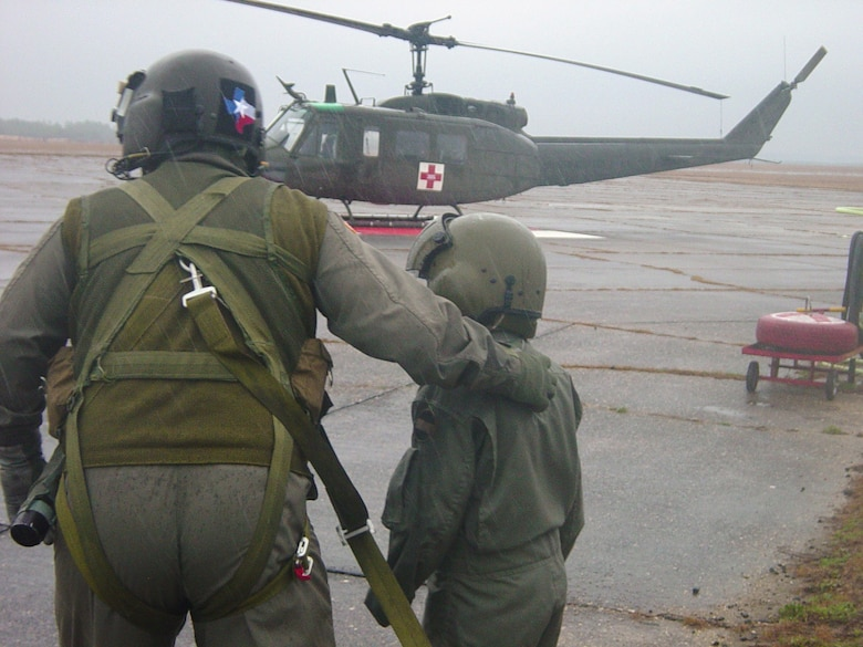 CAMP RUDDER, Fla. -- Riley Woina, 14, from Connecticut, runs through the rain with an air crew member of the 5th Aviation Battalion, Air Ambulance Detachment, Ft. Polk, La., to board a UH-1V Huey helicopter Feb. 21. Riley diagnosed with cystic fibrosis, was granted a week with the 6th Ranger Training Battalion and Eglin Airmen through the Make-A-Wish Foundation Feb. 19-24. (U.S Army photo by Army Capt. Jeremiah Cordovano)