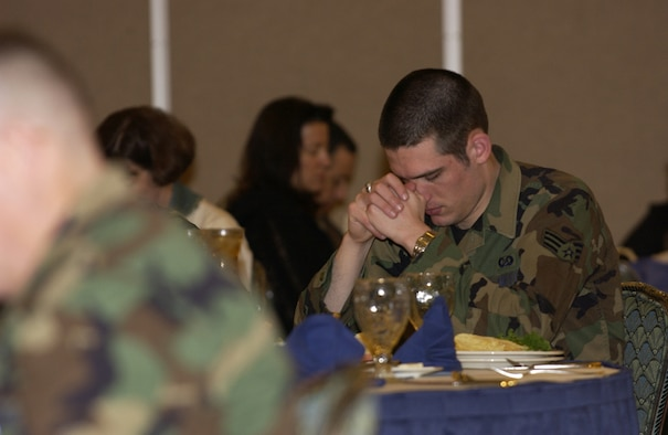 070222- MISAWA AIR BASE, Japan -- An Airman bows his head during prayer at the beginning of Misawa's National Prayer Luncheon Feb. 22 here. Nearly 200 service and family members came out to hear the guest speaker, Chaplain (Colone) Robert Bruno, Joint Chiefs chaplain, give a inspirational message. (U.S. Air Force photo by Senior Airman Robert Barnett)