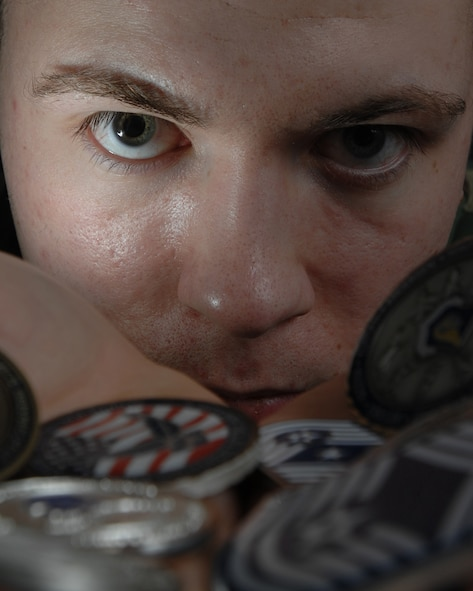 EIELSON AIR FORCE BASE, Alaska -- Airman 1st Class Christopher Griffin, 354th Communication Squadron displays his challenge coins. The challenge coin started during World War I when an American lieutenant ordered solid-bronze medallions and gave it to the pilots in his squadron. (U.S. Air Force photo by Airman 1st Class Jonathan Snyder)