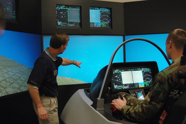 Senior Airman Brian Suminski, with 388th FW manpower, maneuvers in the F-35 simulator while Mr. Mike Barton, a senior staff engineer with Lockheed Martin, guides him on how to fly the aircraft Feb. 22.