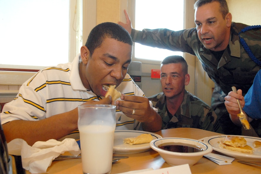 From left to right: Airman 1st Class Kyle Newman, a student in the 312th Training Squadron, prepares to eat another mouthful of pancake while Chief Master Sgt. Paul Moreau, 17th Training Wing command chief master sergeant, and 312 TRS chief military training leader Master Sgt. Mark Brown cheer him on during the 2007 Children's Miracle Network Pancake Eating Contest Tuesday at the International House of Pancakes restaurant in San Angelo. Airman Newman won the contest after devouring 20 pancakes in 20 minutes. Chief Moreau invited Airman Newman to be his designated eater and represent the 17th Training Wing. The contest took place in order to raise awareness and promote community involvement in the Children's Miracle Network, an international non-profit organization dedicated to raising funds for and awareness of children's hospitals. (U.S. Air Force photo by Tech. Sgt. Randy Mallard)