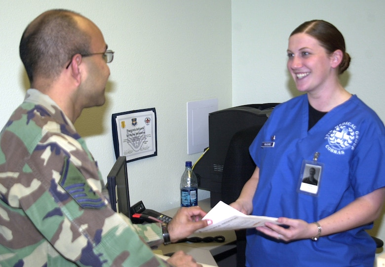"Senior Airman Rachel McAdams (right), a commander's support staff technician with the 17th Medical Group, helps a customer with paperwork Tuesday. Airman McAdams was recently recognized for her volunteer work with Big Brothers Big Sisters of San Angelo, where she works one-on-one as a mentor for her 14-year-old ""little sister."" (U.S. Air Force photo by Airman 1st Class Stephen Musal)"