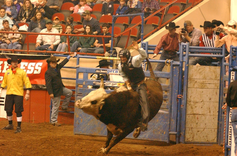 A rodeo competition rider attempts to stay on the bull her rides as the bull tries to toss him off. This was one of several exciting sights volunteers from Goodfellow were treated to at the 2007 San Angelo Live Stock Show and Rodeo Feb. 17. (U.S. Air Force photo by Tech. Sgt. Randy Mallard)