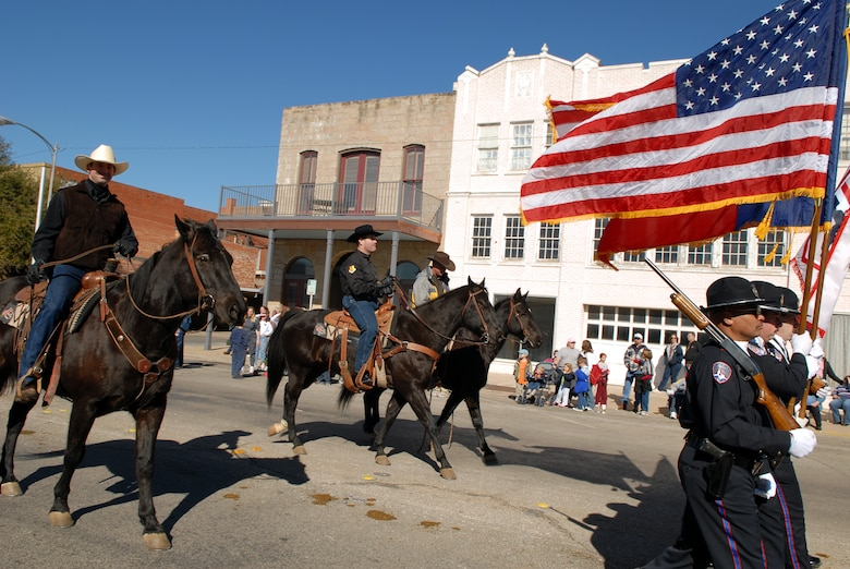 From left to right: Maj. Louis Orndorff, 17th Contracting Squadron commander, and Col. Scott Bethel, 17th Training Wing commander, take part in the 2007 San Angelo Live Stock and Rodeo Parade Feb. 17 in San Angelo. Chief Master Sgt. Paul Moreau, 17 TRW command chief master sergeant, also took part in the parade, riding in a four-wheel all-terrain vehicle. (U.S. Air Force photo by Tech. Sgt. Randy Mallard)