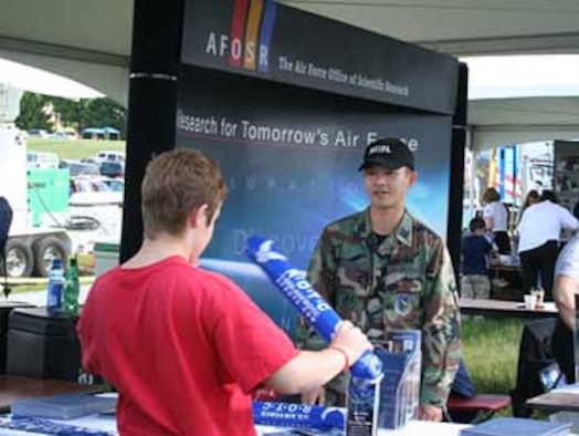 AFOSR Deputy Director of Policy and Integration, Capt. Dan Adcock, talks with a visitor to the AFOSR information booth May 20 at Team America Rocketry Challenge, The Plains, Va. Hundreds of students, parents, and teachers visited the booth throughout the day. ( U.S. Air Force Photo by Erin Crawley)
