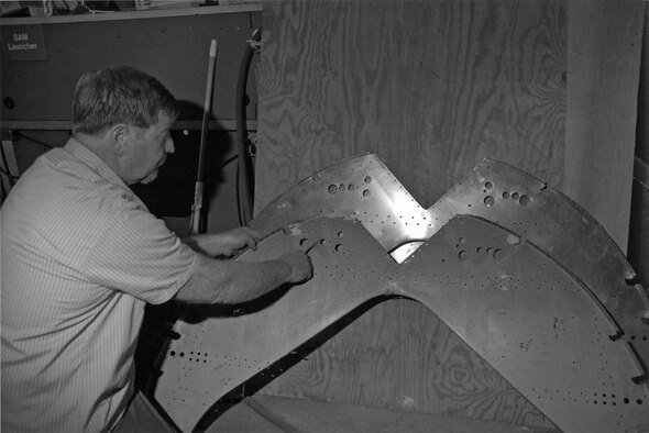 """DAYTON, Ohio - Restoration Specialist Bob Webb points out the corrosion in the frame member of the B-17 """"Memphis Belle."""" The newly pressed frame is behind the item being replaced. (U.S. Air Force photo)"""