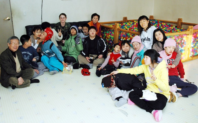 PYONGTAEK, Repulic of Korea --  Senior Airman Kristine Crawley, 51st Maintenance Squadron, (center), spent time with children and adults at a Korean school for the deaf in Pyongtaek on Feb. 1.  Airman Crawley presented enough winter gloves, hats, mittens, scarves and slippers to cloth two dozen people on behalf of the Lt. Col. (retired) Clete Knaub family in Laurel, Mont. (U.S. Air Force photo by Tech. Sgt. Michael O'Connor)