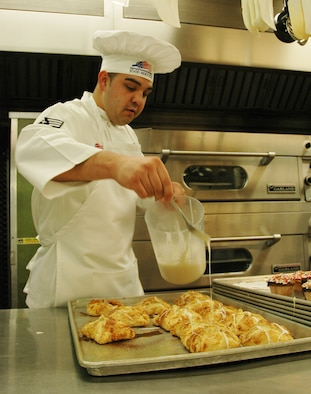 Senior Airman Angelo Apodaca, 302nd Services Flight services technician, applies icing to turnovers at the Aragon Dining Hall. (U.S. Air Force photo by Tech. Sgt. Tim Taylor)