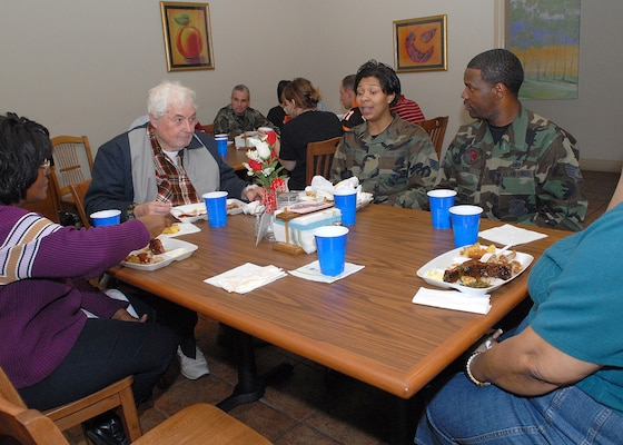 Ramana Lewis, left, Fisher House staff member, Howard Atwell, patient, Staff Sgt. Marcia Strickland-King, 37th Training Wing, and Staff Sgt. Gregg King, 37th Mission Support Squadron, share a meal at the Lackland Fisher House Feb. 15. The African-American Heritage Committee volunteered at the home on Lackland Air Force Base, Texas, as one of 10 planned activities in February, African-American History Month. (USAF photo by Robbin Cresswell)