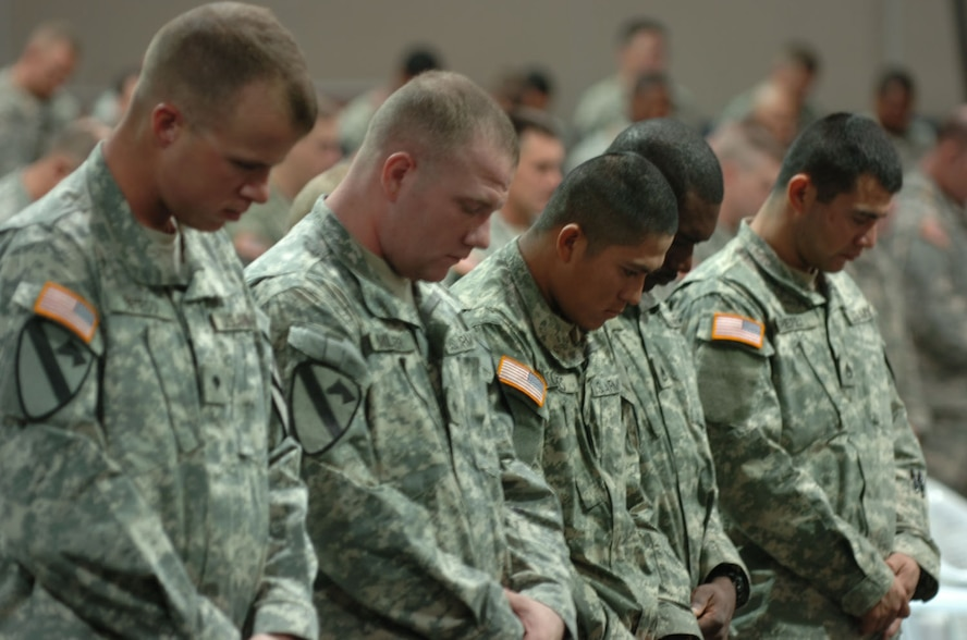 Soldiers bow their heads in honor of their fallen comrade, Army Staff Sgt. Daniel Morris, during his memorial at a Forward Operating Base in Iraq, Nov. 27, 2006.