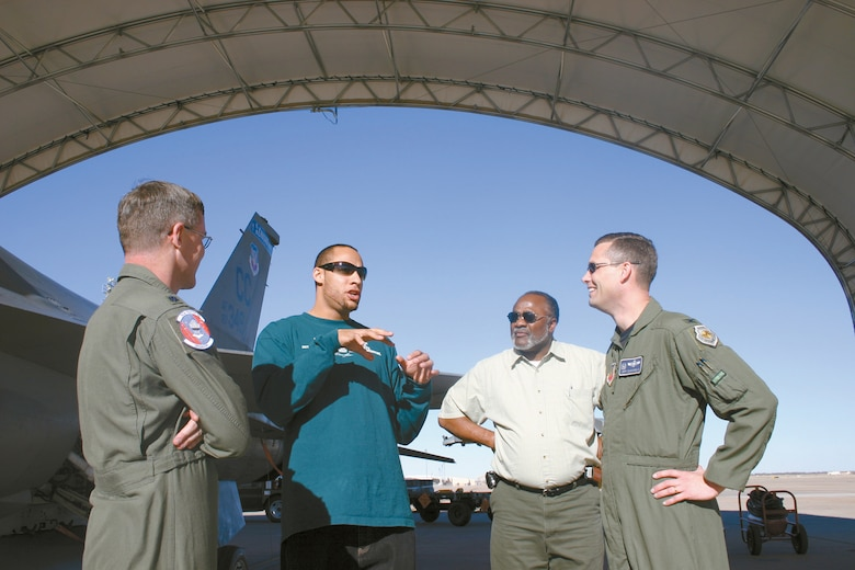Lt. Col. Brad Kearney; 523rd Fighter Squadron commander and Col. Jeff McDaniel, 27th Operations Group commander at Cannon Air Force Base, N.M., listen as Hank Baskett III (second from left) explains how the sound of an F-16 flying overhead compares with the sound of the crowd at a football game. Hank and his father, retired Chief Master Sgt. Hank Baskett Jr. (second from right) toured the 523 FS and the flight simulator on Feb. 21. The retired chief's  son finished his first National Football League season with the Philadelphia Eagles as a wide receiver where he received the Rookie of the Week award twice during the season. (U.S. Air Force photo by Janet Taylor-Birkey)
