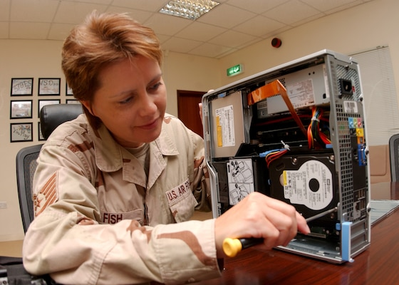 Tech. Sgt. Tia Fish, a client support administrator and NCOIC of the commander support staff, performs maintenance on a computer. Computer system maintenance in deployed locations such as Sergeant Fish's can be challenging due to dusty conditions. Sergeant Fish is deployed from the 19th Air Force Initial Flight Screening office. (Courtesy photo)