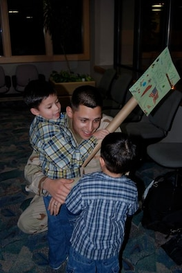 """Staff Sgt. James Prim, 28th Civil Engineer Squadron, hugs his sons Diego and Robert, after returning Dec. 22 from a 7-month deployment to Contingency Operating Base Speicher, Iraq. Sergeant Prim was one of 42 28th CES Airmen deployed in support of the continuing global war on terrorism and responsible for maintaining base infrastructure in their overseas location. We left with a big sense of accomplishment, said Sergeant Prim. """"I think we put a big dent in the workload, but there's a lot of work to be done yet."""""""