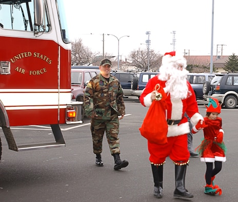 """Misawa AB, Japan -- Santa Clause and his elf helper are escorted to the Commissary in style by the 35 Civil Engineering Squadron for the annual """"Picture with Santa"""" at Misawa Air Base, Japan on December 23, 2006.  (U.S. Air Force photos by Senior Airman Laura R. McFarlane)"""