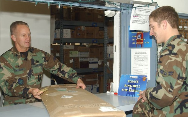 MISAWA AIR BASE, Japan -- Col. Arnie Holcomb, 35th Mission Support Group commander, hands a Misawa post office customer his package. Colonel Holcomb is helping the post office staff during the holiday season. The post office requests volunteers to help during the holiday season when they receive the most incoming and outgoing mail. (USAF photo by Airman Benjamin Wilson)