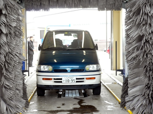 MISAWA AB, JAPAN -- Brig. Gen. Sam Angelella, 35th Fighter Wing and installation commander, takes his wife's  vehicle through the new car wash near the main base gas station after the ribbon cutting ceremony Dec. 29. The 24-hour yen coin-operated car wash has two stalls -- one is automated and the other is manual. The facility cost nearly $650,000 to build. The cost to wash a vehicle ranges from 100 for four minutes in the manual stall and 200 yen for the automated wash.