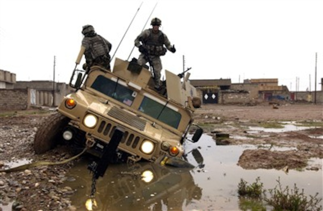 U.S. Army soldiers dismount from their Humvee after getting stuck in a mud hole while patrolling through Kirkuk, Iraq, on Dec. 28, 2006.  The soldiers are from Charlie Company, 2nd Battalion, 35th Infantry Regiment, 25th Infantry Division.