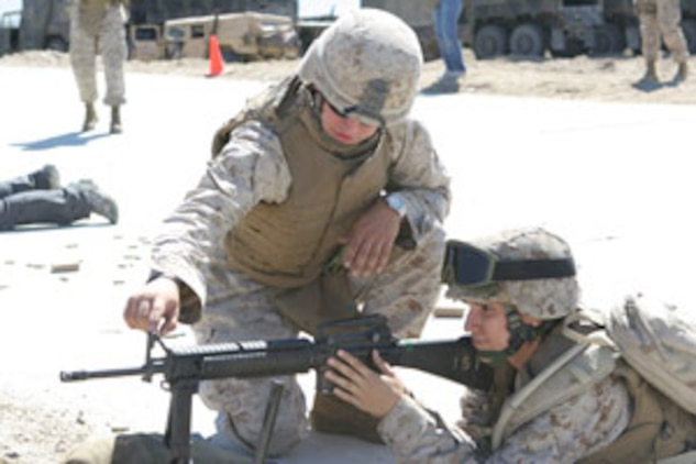 Lance Cpl. Devon Preiser, Jane Wayne Day range coach, gives Alicia Lara a crash course in correct sight alignment of the M-16 rifle at the Combat Center?s Range 500 during the 1st Tank Battalion Jane Wayne Day Oct. 4.