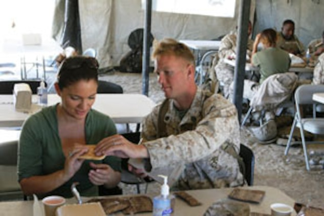 Staff Sgt. Nicholas Macdonald shows his wife, Esther, how to eat the food from a Meal-Ready-to-Eat at the Combat Center?s Range 500 during the 1st Tank Battalion Jane Wayne Day Oct. 4.