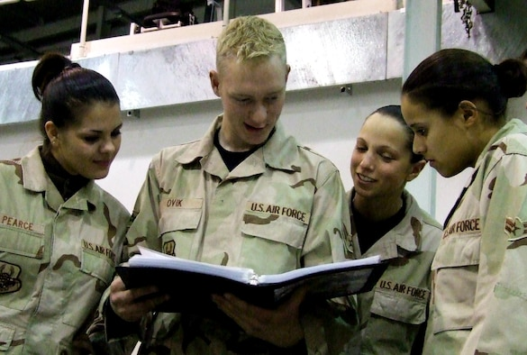 BALAD AIR BASE, Iraq-- (From left to right) Senior Airman Natalie Pearce, Airmen 1st Class Dave Ovik, Brianna Bloomquist and Jessica Canabal examine the book of letters sent by members of the Travis civilian community. Lt. Gen. Gary North, USCENTAF commander, presented the letters to Airmen Dec. 28. All the Airmen are deployed from the 60th Aerial Port Squadron at Travis Air Force Base, Calif. (U.S. Air Force photo by Maj. Richard Sater/332nd AEW Public Affairs)