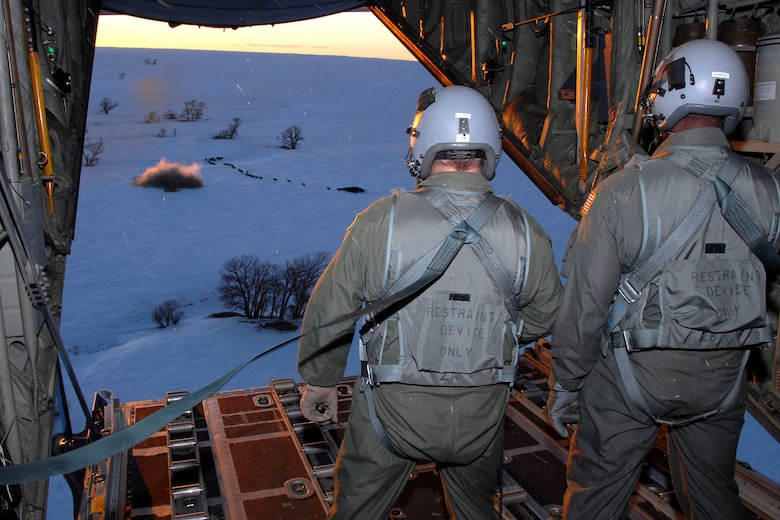 Loadmasters of the Wyoming Air National Guard watch a one-ton hay bale land near a herd of cows during an emergency feeding mission Jan. 3 caused by a snowstorm that hit the area in southeastern Colorado. (U.S. Air Force photo/Senior Master Sgt. John Rohrer)