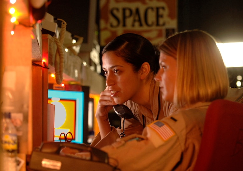 Staff Sgt Cristina Kavanagh and 1st Lt. Tanya Frazier provide space-based theater ballistic warning to U.S. forces in the Southwest Asia theater from the Combat Operations Space Cell inside the Combined Air Operations Center. They also run Global Positioning Satellite predictions to ensure GPS accuracy and support combat search and rescue missions when necessary via space support. Sergeant Kavanagh is a space duty technician from Buckley Air Force Base, Colo., and Lieutenant Frazier is a space duty officer from F.E. Warren AFB, Wyo. (U.S. Air Force photo/Master Sgt. Scott Wagers)