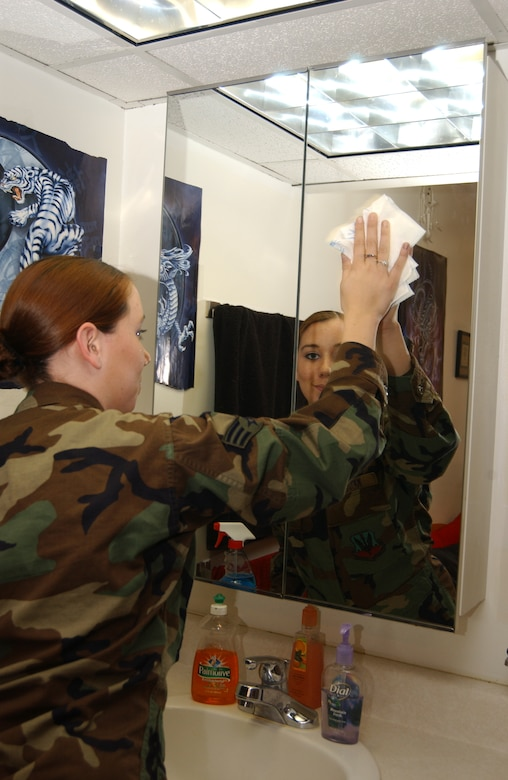 Senior Airman Christina Kessler, 4th Communications Squadron, cleans the mirror in her dorm room Dec. 15. Airman Kessler won Room of the Quarter in a competition dormitory-wide. (U.S. Air Force photo by Airman 1st Class Shane Dunaway)