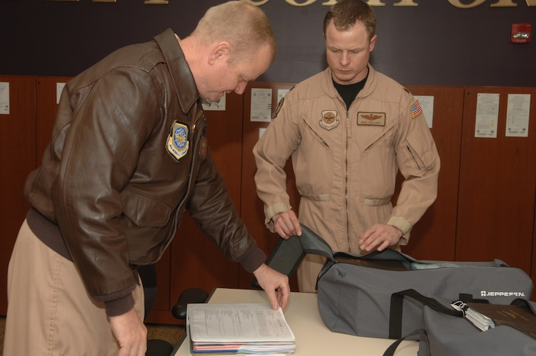 ANDREWS AFB, Md. -- Lt. Col. Chris J. Kampsen and Maj. Michael T. Dellert, 99th Airlift Squadron C-20 pilots, discuss and pack flight materials needed for their mission prior to departing on their deployment.