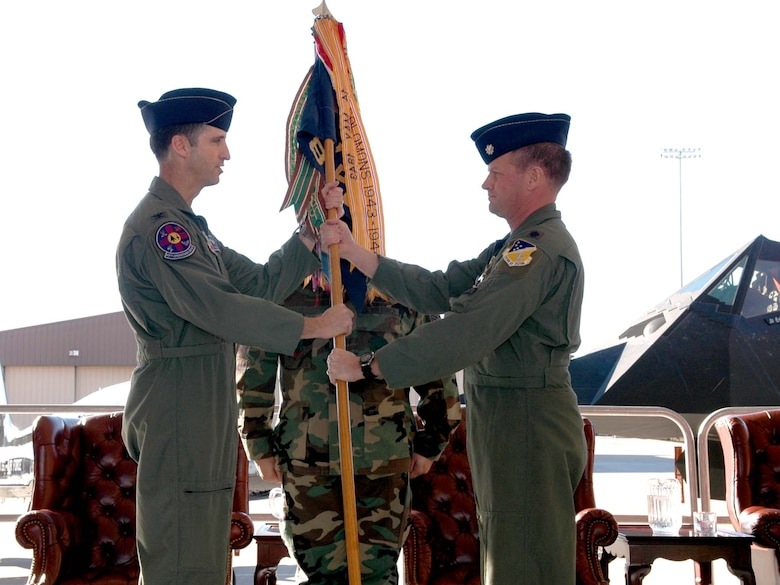 Col. Jack Forsythe, 49th Operations Group commander, hands the 8th Fighter Squadron guidon to Lt. Col. Christopher Williams, new 8 FS commander, signifying the change of command in a ceremony Jan. 5. (U.S. photo taken by Airman Jamal Sutter)