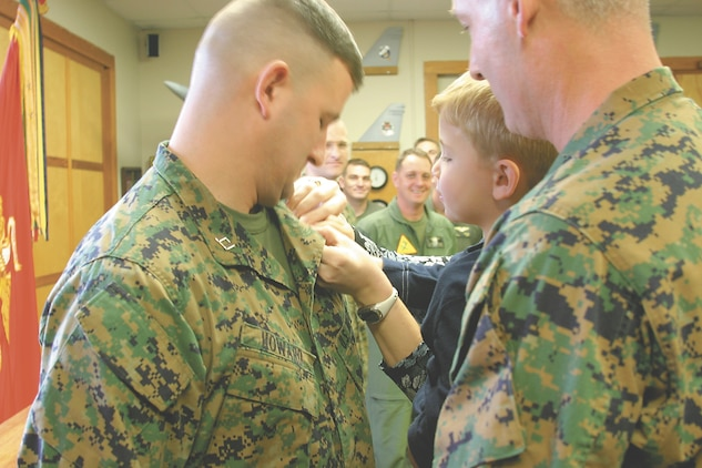 Capt. Ray Howard, the Marine Aircraft Group 31 embarkation officer, has his new rank pinned on by his three-year-old son and his former commanding officer, Col. James Hooks, the commanding officer of the Blount Island Command, here March 1. Howard enlisted in the Marines in 1994 and has worked his way up the ranks to become a captain as a limited duty officer.