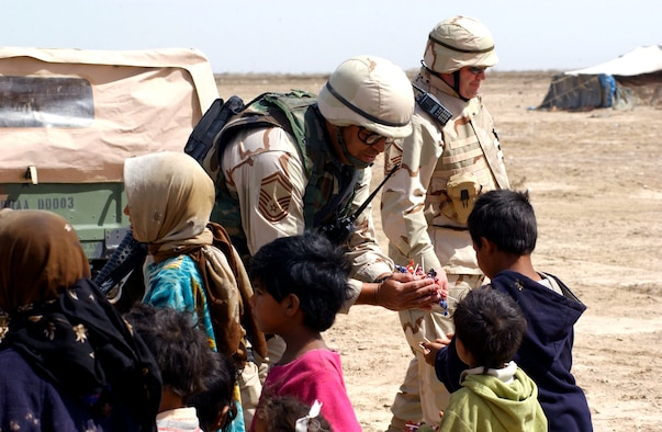 NEAR TALLIL AIR BASE, Iraq -- Senior Master Sgt. Robert Appling hands out candy to children during a visit to Bedouin camps here.  He is the fire chief assigned to the 407th Expeditionary Civil Engineer Squadron.  (U.S. Air Force photo by Master Sgt. Mark Bucher)