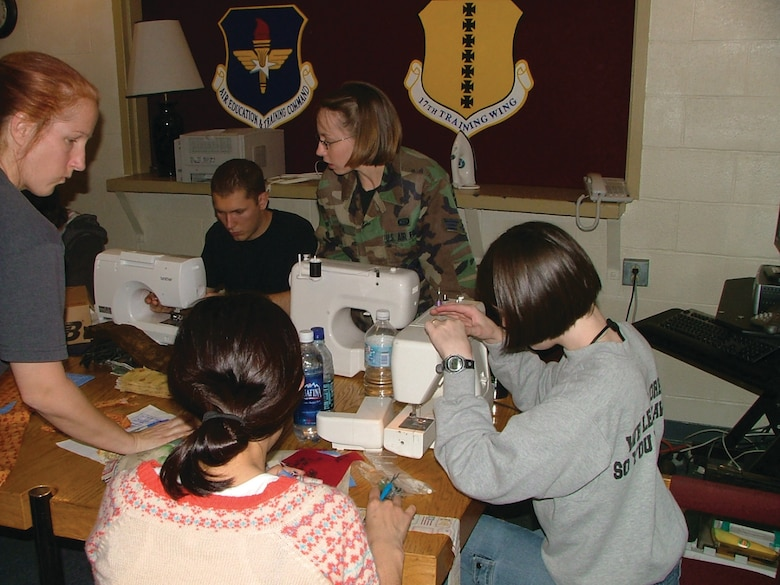 Chief Academic Training Advisor Master Sgt. Susan Boyd led a group of approximately 30 airmen sewing quilts for wounded soldiers and airmen.  311th students and staff members write messages of hope and inspiration on quilt squares for service members wounded in action.