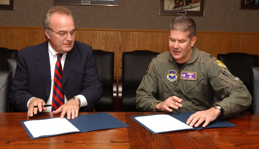 The commander of the 17th Training Group, Col. Scott George, and Mr. Wallace Boston, President of the American Public University System and American Military University, sat down to sign a memorandum of understanding Tuesday.