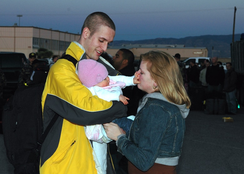 Airman 1st Class Bret Mills, 49th Maintenance Squadron, says goodbye to his wife, Stephanie, and his daughter, Gianna, 8 months, before he deploys to Korea Monday. More than 300 Airmen are going on this deployment from Holloman (U.S. Air Force photo by Airman Jamal Sutter)