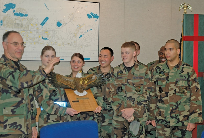 EIELSON AIR FORCE BASE, Alaska--The 4th Quarter Dorm Excellence Competition winners receive the winning plaque from Brig. Gen. Dave Scott, 354th Fighter Wing commander, at the Jan. 4 wing staff meeting. The winning dormitory was building 2353, housing single Airmen from the 354th Medical Group, 354th Operations Squadron, 354th Services Squadron, 354th Comptroller Squadron and Detachment 460.