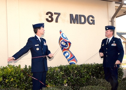 Brig. Gen. Darrell Jones, then the 37th Training Wing commander, and Col. Tim Halligan, then the commander of the newly reactivated 37th Medical Group, unveil the group's abbreviation on its headquarters building across Biggs Avenue from the Warhawk Fitness Center. General Jones led the Dec. 22, 2006, ceremony to reactivate the group, the first medical assets under direct control of the 37th TRW since Wilford Hall Medical Center was completed in 1957. (USAF photo by Robbin Cresswell)