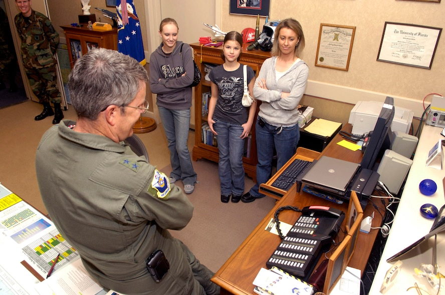Maj. Gen. Jeffrey Riemer, program executive officer for weapons and Air Armament Center commander, congratulates Tech. Sgt. Dennis Barnett, 96th Security Forces Squadron, on his Stripes For Exeptional Performers promotion Jan. 9 while his wife and daughters look on. Sergeant Barnett is currently deployed.