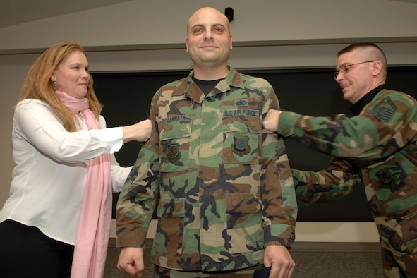 Katherine Cannata, wife of now Master Sgt.  George Cannata, tacks on her husband?s new stripes along with Senior Master Sgt. Daniel North, 92nd Aircraft Maintenance Squadron first sergeant. Sergeant Cannata, 92nd AMXS maintenance operations exec, was STEP promoted to the rank of master sergeant Dec. 15.