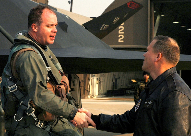 "Col. Jeff Lofgren (right) greets Maj. Ronald Keller after landing Jan. 11 at Kunsan Air Base, Korea. Major Keller, an F-117 Nighthawk pilot, is part of a more than 300-person deployment to Kunsan from Holloman Air Force Base, N.M. Assigned to the 9th Expeditionary Fighter Squadron, the Holloman AFB Airmen are fulfilling an Air Expeditionary Force rotation to the Republic of Korea. The AEF deployment, according to Kunsan AB officials, ""demonstrates the continued U.S. commitment to fulfill its security responsibilities throughout the Western Pacific."" Colonel Lofgren is the 8th Fighter Wing commander. (U.S. Air Force photo/Senior Airman Stephen Collier)"