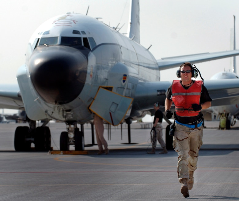 Staff Sgt. James Parker runs to the middle of the taxiway to martial an RC-135 Rivet Joint reconnaissance aircraft that is departing for a mission over Southwest Asia. Sergeant Parker is a crew chief deployed from the 55th Aircraft Maintenance Squadron, Offutt Air Force Base, Neb. (U.S. Air Force photo/Master Sgt. Scott Wagers)
