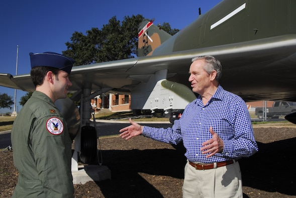 Texas Air National Guard Maj. Jon Stone, a pilot in the 149th Fighter Wing, listens to his father, retired Air Force Col. John Stone, describe flying missions he executed in F-4 aircraft like the static display behind them. Colonel Stone visited the wing on Lackland Air Force Base Jan. 5. (Texas National Guard photo by Senior Master Sgt. Mike Arellano)