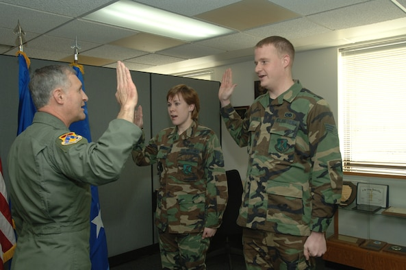 Maj. Gen. James Hawkins, 18th Air Force commander, re-enlists two Airmen. (photo/Airman 1st Class SerMae Lampkin)