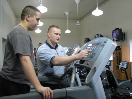 MCCHORD AIR FORCE BASE, Wash. -- Personal trainer Staff Sgt. Noah Grayson, 62nd Services Squadron, works with Airman 1st Class Travis Morrill, 62nd SVS, to select the appropriate settings on a treadmill so that Airman Morrill can get a good cardiovascular workout at the Fitness Center Annex recently.(U.S. Air Force Photo/Staff Sgt. Tiffany Orr)